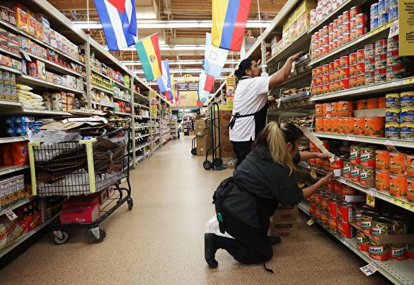 圖為加州一家超市的員工在補貨。(Mario Tama/Getty Images)