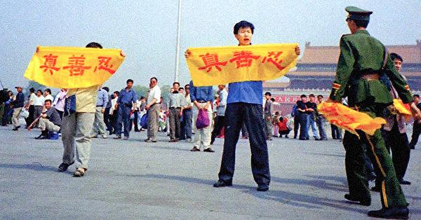 1999年7月,中共對法輪功發動滅絕性的迫害後,成千上萬的法輪功學員冒著生命危險在北京天安門廣場上和平請願,打出寫著中文「真、善、忍」的橫幅。圖中顯示一名準備抓人的中共警察,手上還拿著從其他學員手中奪下的橫幅。(明慧網)