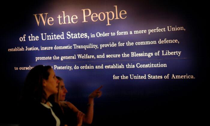 2003年7月1日,賓夕凡尼亞州費城的國家憲法中心,兩名婦女走過一幅美國憲法的畫作。(William Thomas Cain/Getty Images)