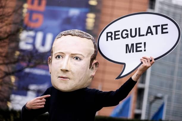 2020年12月15日,在布魯塞爾的歐盟委員會大樓外,一名環保活動家戴著面書創始人朱克伯格的面具舉牌抗議,牌子上寫著:監管我。(KENZO TRIBOUILLARD/AFP via Getty Images)