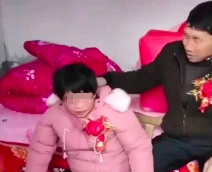 日前,河南一段婚嫁影片在網絡熱傳。影片中,一疑似未成年女子嫁給一位大叔,女子大聲哭喊。(影片截圖)
