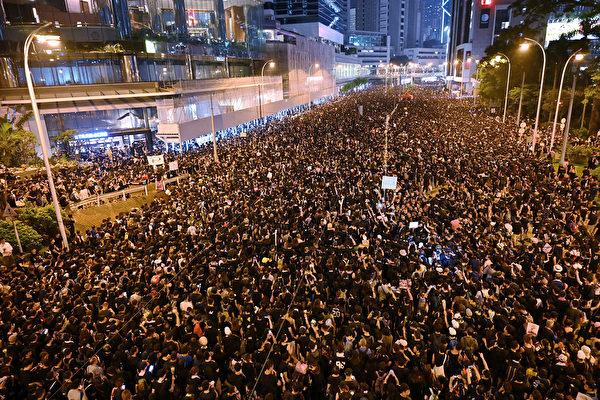 6月16日,大批香港民眾走上街頭繼續抗議惡法,即使香港夜幕降臨,抗議人群仍未散去,依然聲勢浩大,要求撤回惡法。(HECTOR RETAMAL/AFP)