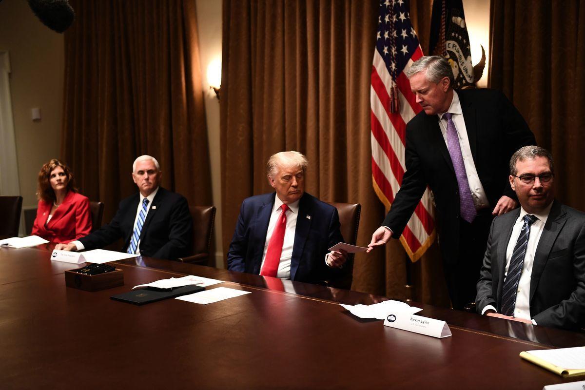圖為2020年8月3日禁止聯邦機構解僱美國人,改用外勞的行政令簽署儀式上,總統特朗普接到便簽通知;便簽上說,解僱美國人的一家美國大型國有企業剛來電表示,「願意改變」其裁員決定。(BRENDAN SMIALOWSKI/AFP via Getty Images)