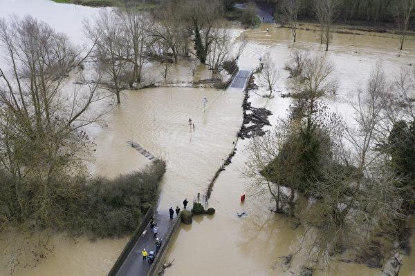 2020年12月26日,英國貝德福德帕文漢姆(Pavenham),大烏斯河(Great Ouse)氾濫成災,民眾正看著高漲的水位。(Dan Kitwood/Getty Images)