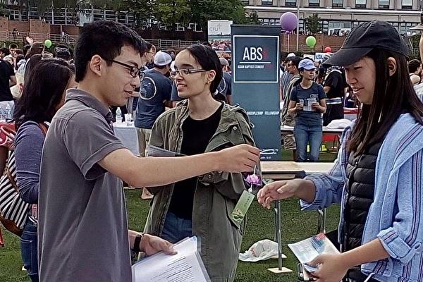 美國波士頓大學學生在社團博覽會上了解法輪功真相。(明慧網)
