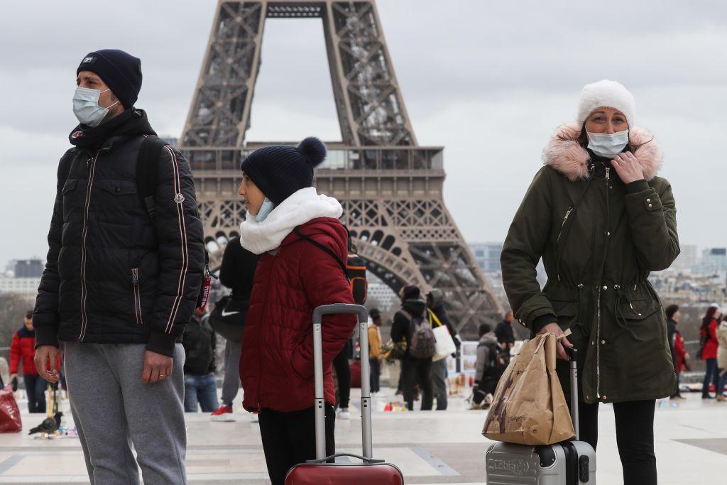 2020年3月12日,佩戴口罩的遊客在巴黎的埃菲爾鐵搭前。(LUDOVIC MARIN/AFP via Getty Images)