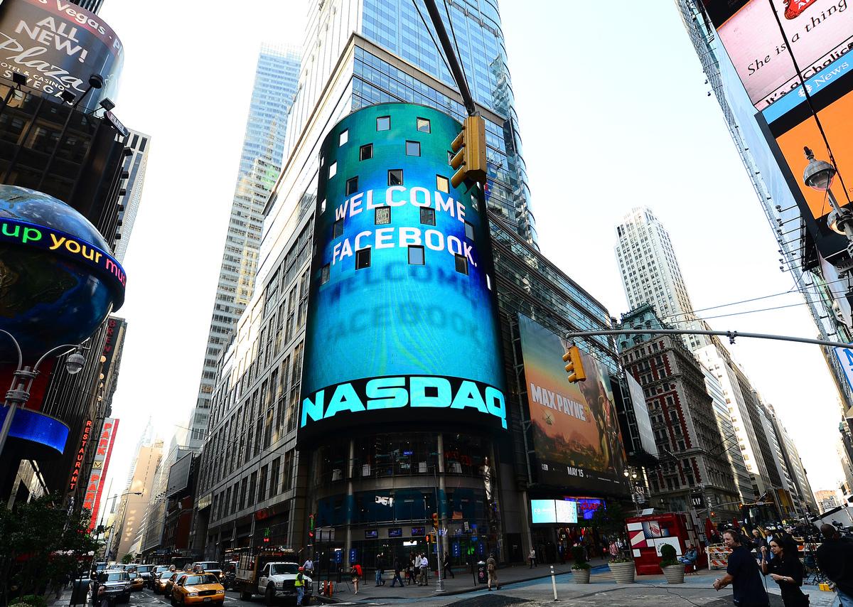 圖為2012年5月18日,紐約時代廣場納斯達克證券交易所外的屏幕上閃爍著歡迎Facebook的標誌。(EMMANUEL DUNAND/AFP via Getty Images)