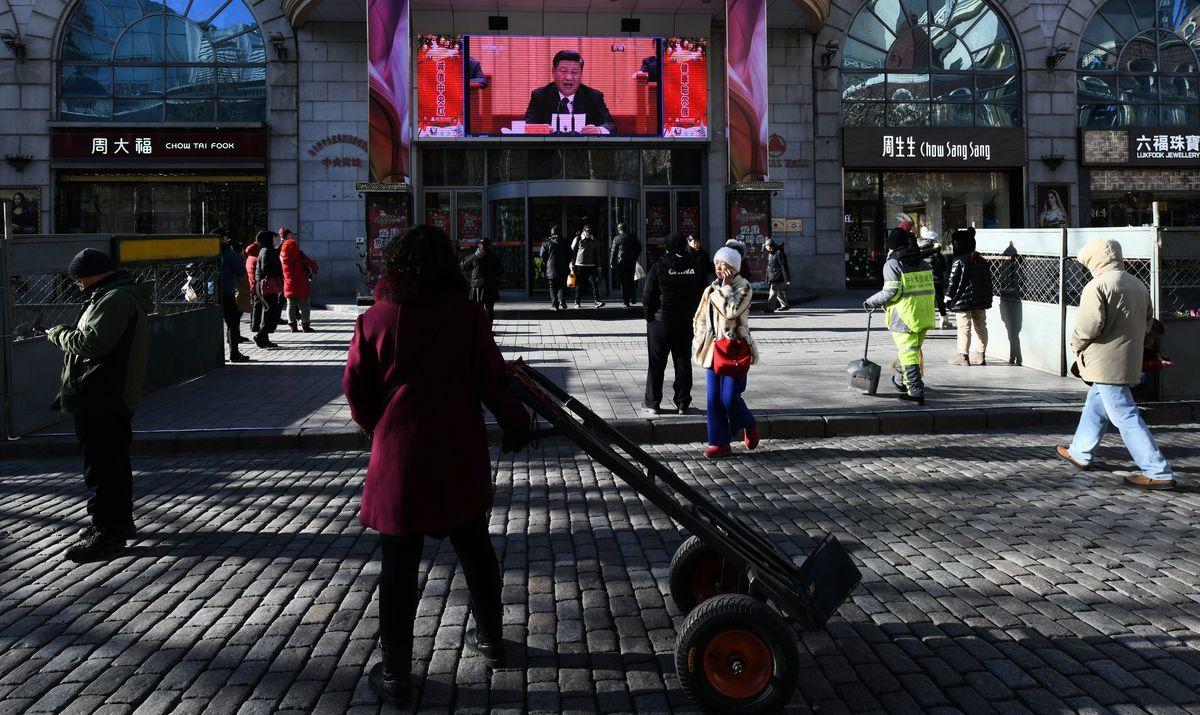 12月18日北京街頭,行人在觀看習近平在北京改革開放40周年大會上講話的大屏幕。(Tao Zhang/Getty Images)