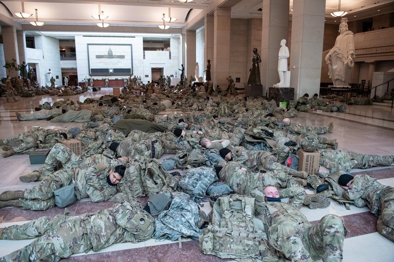 美國從各州抽調了2.5名國民警衛隊士兵來到華府。圖為1月13日國民警衛隊士兵在華盛頓特區國會山的國會遊客中心大廳裏休息。(SAUL LOEB/AFP)