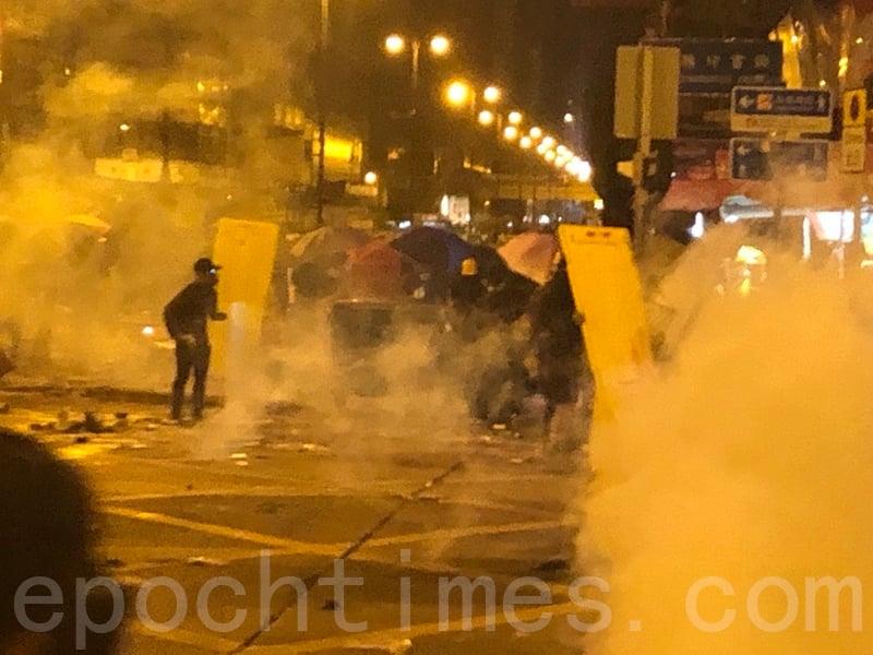 11月18日晚,成千上萬的民眾趕往理大救援被困的學生,港警在佐敦道、彌敦道的交界處狂射催淚彈驅趕民眾。(余天祐/大紀元)
