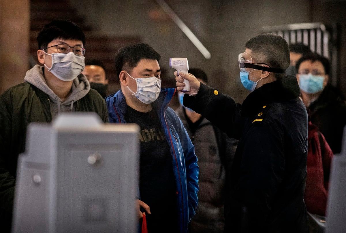 武漢封城被指形成了外逃的浪潮,加劇了疫情蔓延。圖為2020年1月23日,一名醫務人員對從武漢到北京的最後一班列車的乘客做體溫測試。(Kevin Frayer/Getty Images)