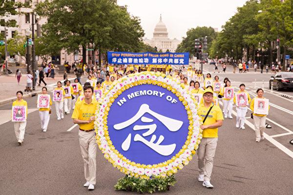 在華盛頓DC舉行的反迫害遊行中,法輪功學員手捧相片,悼念在中國被迫害致死的法輪功學員。(明慧網)