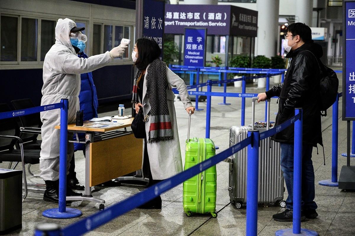 圖為2020年2月4日,上海浦東國際機場的安全人員量測旅客的體溫。(NOEL CELIS/AFP via Getty Images)