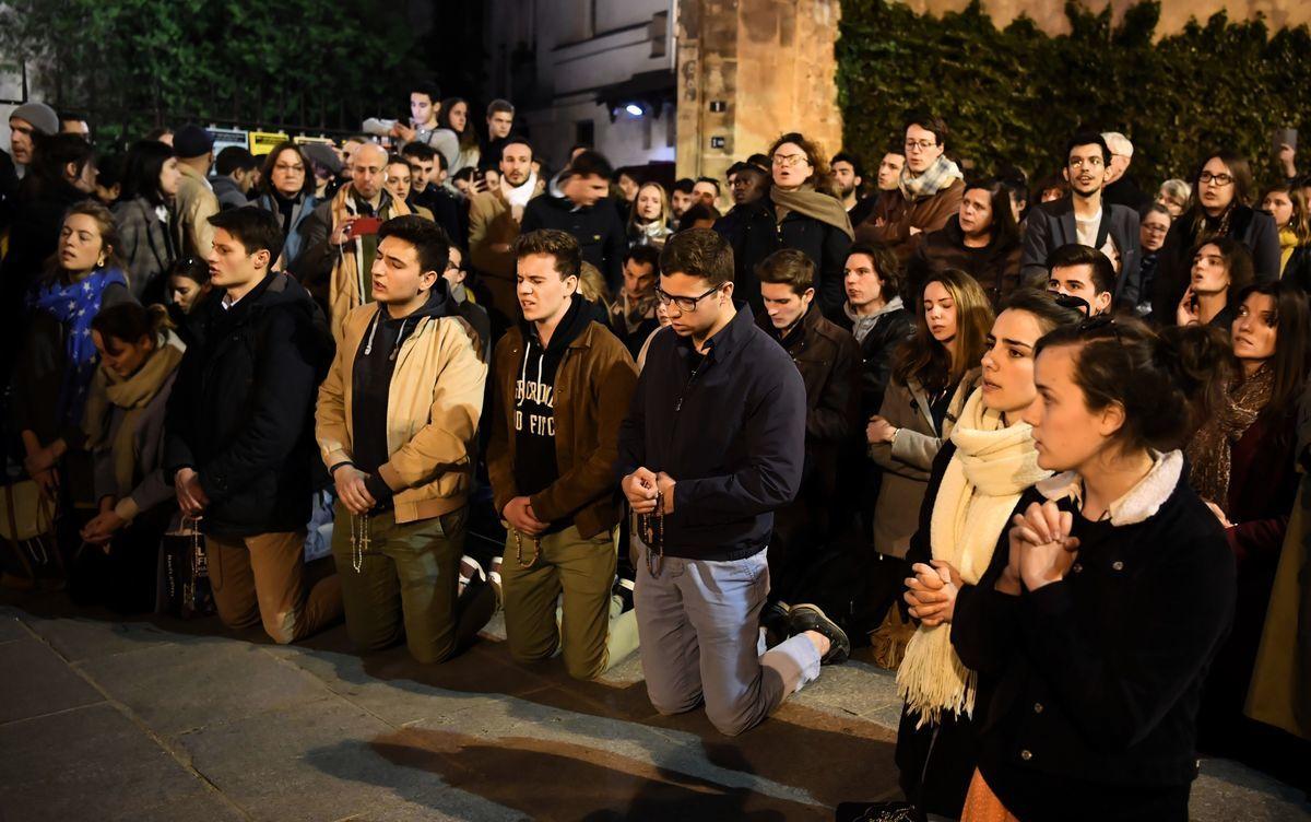 周一(4月15日),法國巴黎著名地標聖母院失火,巴黎人傷心欲絕地哭了,跪地為聖母院祈禱。(ERIC FEFERBERG/AFP)