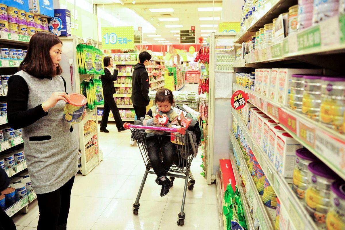 三鹿毒奶粉後,中國劣質奶粉、空奶粉罐回收假奶粉、固體飲料冒充特醫奶粉等事件多發,讓中國媽媽憂心忡忡。圖為2017年2月14日,一位中國消費者在山東省青島的一家超市選擇奶粉。(STR/AFP/Getty Images)