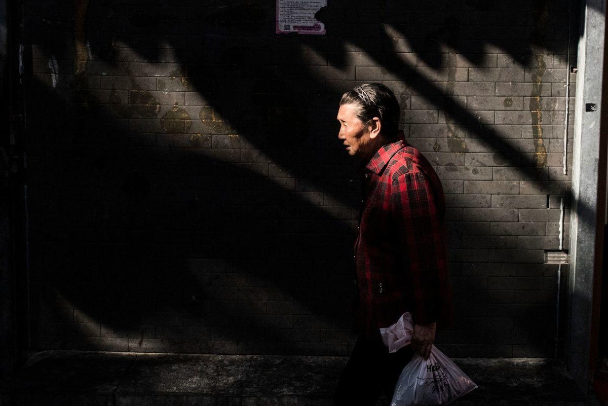 中國一胎化政策導致社會人口老齡化嚴重,而且更有未富先老的慘現象。圖為北京一位老人走過街頭。(FRED DUFOUR/AFP/Getty Images)