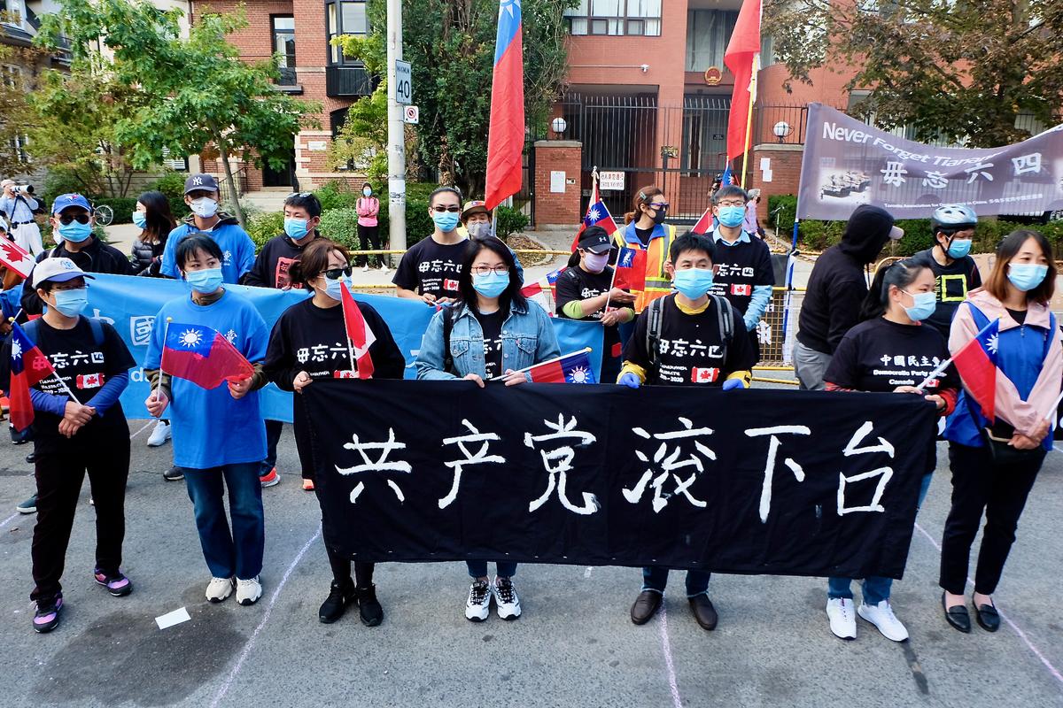 10月1日,在多倫多參加集會的民眾舉橫幅,上面寫著「共產黨滾下台」。(周月諦/大紀元)