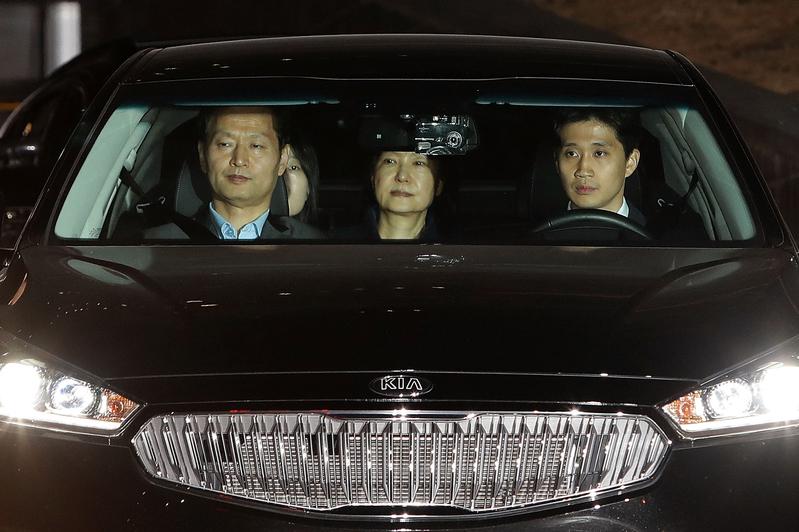 2017年3月31日,朴槿惠(後中)坐在開往首爾拘留所的車後座。(CHUNG SUNG-JUN/AFP)