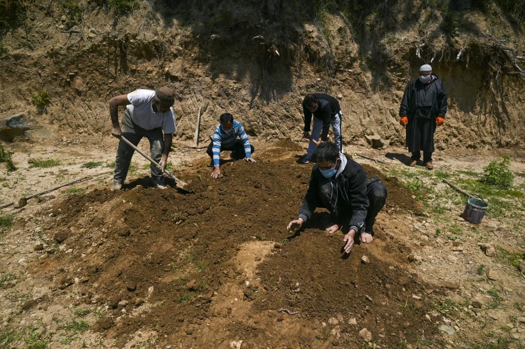 周四(4月29日),印度感染COVID-19的人數超過了1,800萬,且周四單日又有創紀錄新增病例。同時染疫死亡人數居高不下,墓園工人全天候工作掩埋死者。(Tauseef MUSTAFA/AFP)