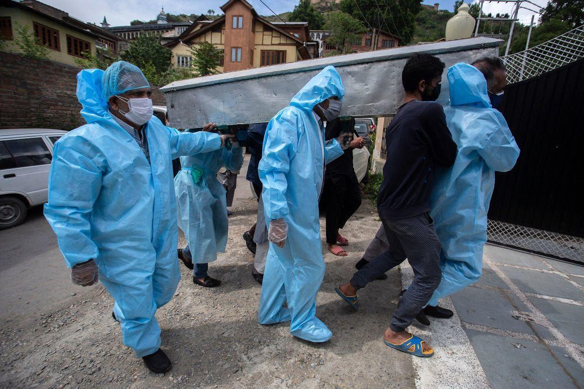 2021年5月7日,印度斯利那加(Srinagar)的送葬隊伍中,身著防護裝備的親屬抬著一名死於Covid-19的受害者遺體。(ABID BHAT/AFP via Getty Images)