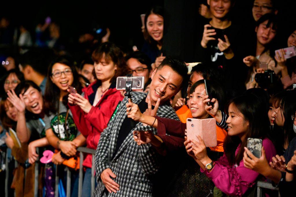 中共宣佈抵制今年的台北金馬獎影展,引發關注。圖為去年11月金馬獎影展上,影星和觀眾互動的情景。(SAM YEH/AFP/Getty Images)