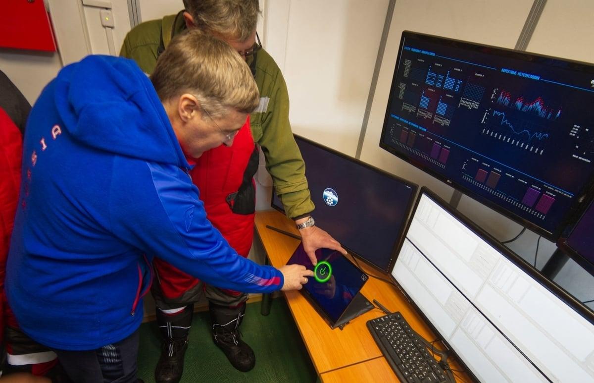 俄羅斯科學家和官員正在通過屏幕觀看將中微子望遠鏡放置到貝加爾湖水中的操作過程。(Bair Shaibonov/Russian Institute for Nuclear Research/ AFP)