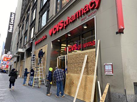 時代廣場附近的CVS藥店正在店外釘木板。(張本真/大紀元)