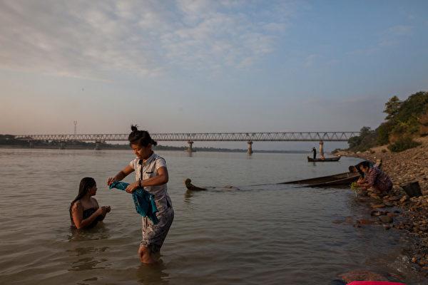 2013年12月28日,緬甸克欽邦(Kachin)的居民正在日落時分的伊洛瓦底江(Irrawaddy River)中沐浴。伊洛瓦底江是緬甸生命線。該河為下游的濕地和洪泛區提供了重要養分,包括為緬甸提供了近60%大米產量的三角洲地區。不顧當地人強烈反對,中共要在這條江上建設一個大規模水電項目。2011年,在緬甸總統的授權下,該水電大壩項目被暫停。(Diana Markosian/Getty Images)