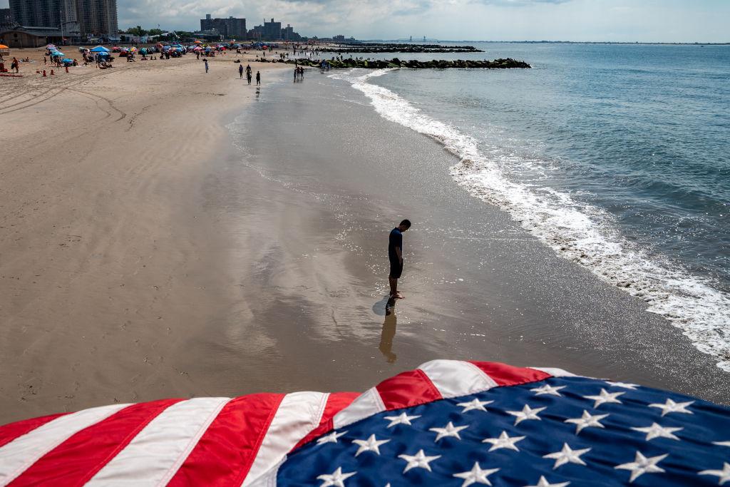 2021年7月4日,紐約康尼島海灘上的一個人若有所思。美國紀念第245個獨立日之際確實需要反思。(David Dee Delgado/Getty Images)