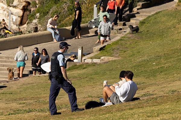 在澳洲悉尼邦迪海灘(Bondi Beach),一名警官在維持公共衛生秩序行動中與一名遊人交談。2021年8月15日攝。(Brook Mitchell/Getty Images)