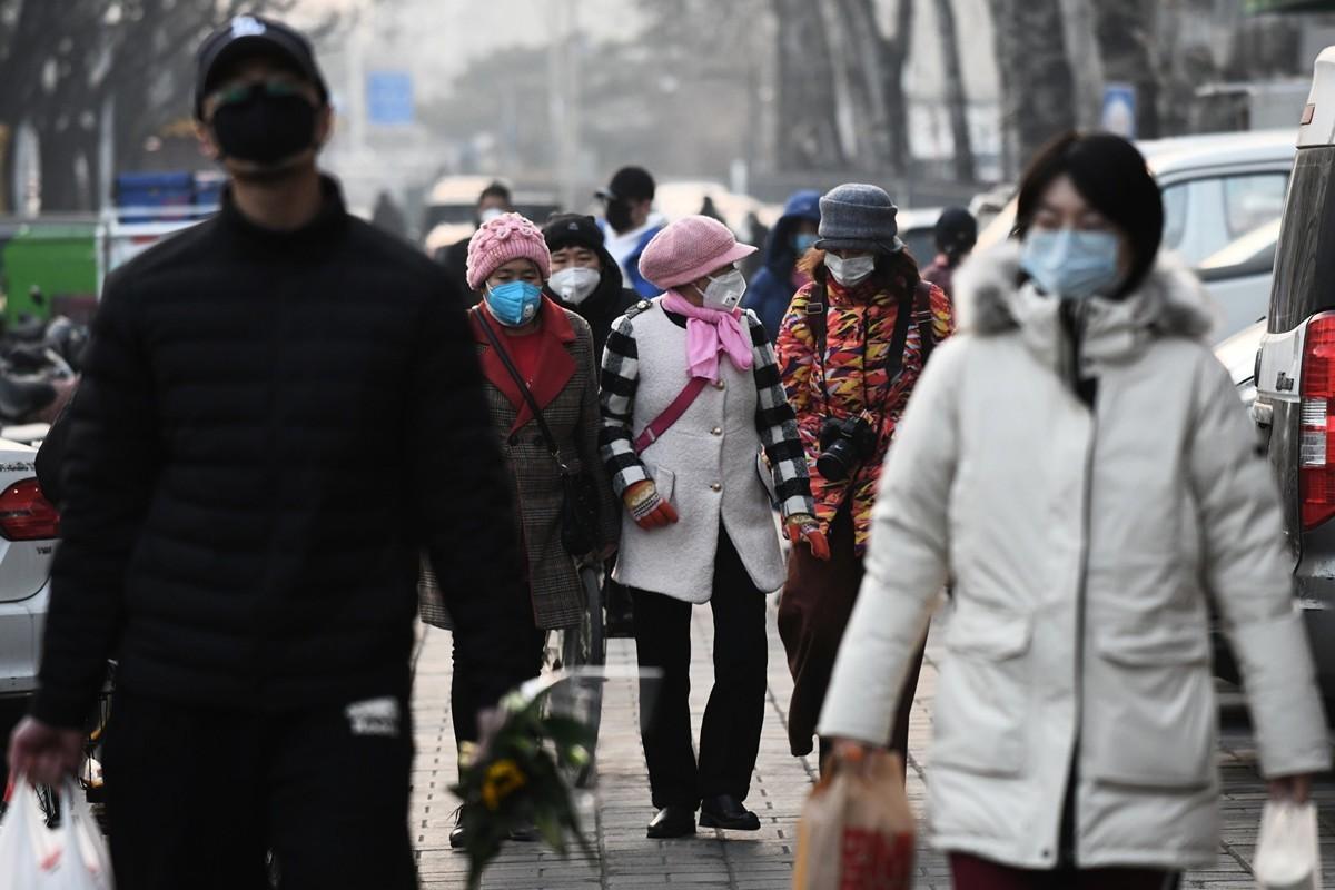 有大陸民眾故意用口水傳播病毒,引起公憤。圖為2020年2月9日,北京街頭戴口罩的行人。(GREG BAKER/AFP via Getty Images)