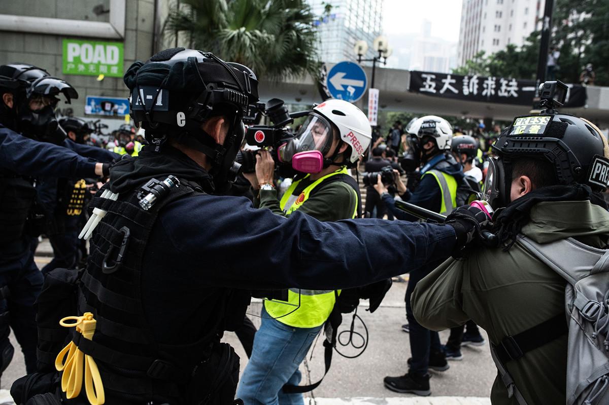 2020年1月19日,香港警察在動手干預一群正在「天下制裁」集會中工作的現場記者。(Philip FONG/AFP)