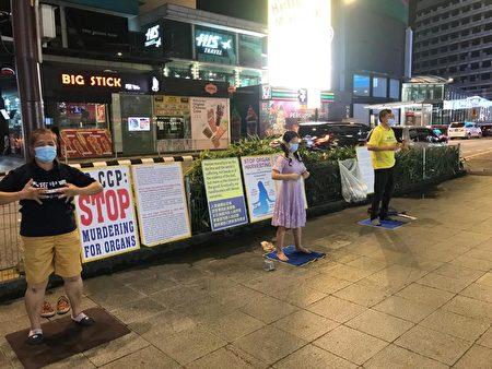 馬來西亞部份法輪功學員在吉隆坡市中心掛展板、煉功,向民眾講真相。 (Peter Ong/大紀元)