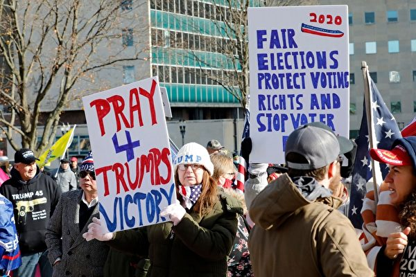2020年11月14日,在密歇根蘭辛,民眾聚集在州議會大廈外,抗議大選舞弊,要求制止竊選。圖為一位民眾舉著展板呼籲為特朗普總統勝選祈禱。(JEFF KOWALSKY/AFP via Getty Images)