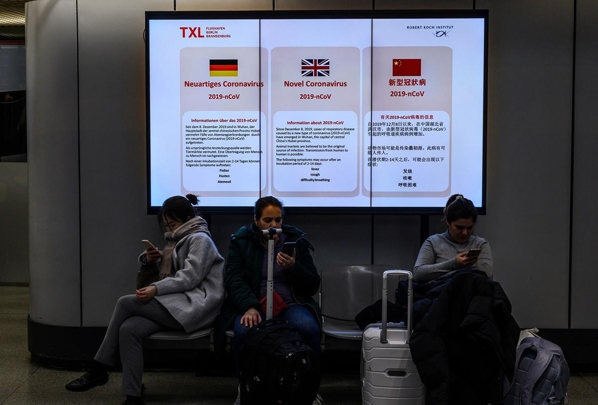 今年1月底,柏林泰格爾機場內一個屏幕上顯示多語種關於中共病毒的信息。(JOHN MACDOUGALL/AFP via Getty Images)
