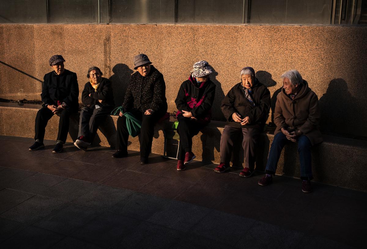 中共兩會,江西一人大代表建議讓已退休的獨生子女父母在子女工作生活地落戶,並享受當地居民同等待遇。圖為2019年11月8日北京,一群在夕陽中的老人們在聊著天。(Kevin Frayer/Getty Images)