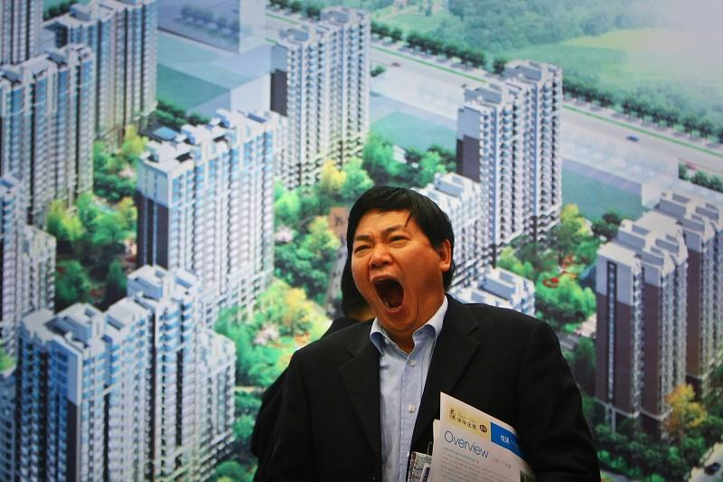 一名參觀者在北京秋季房地產交易會城市建築模型前打哈欠。(Photo by Feng Li/Getty Images)