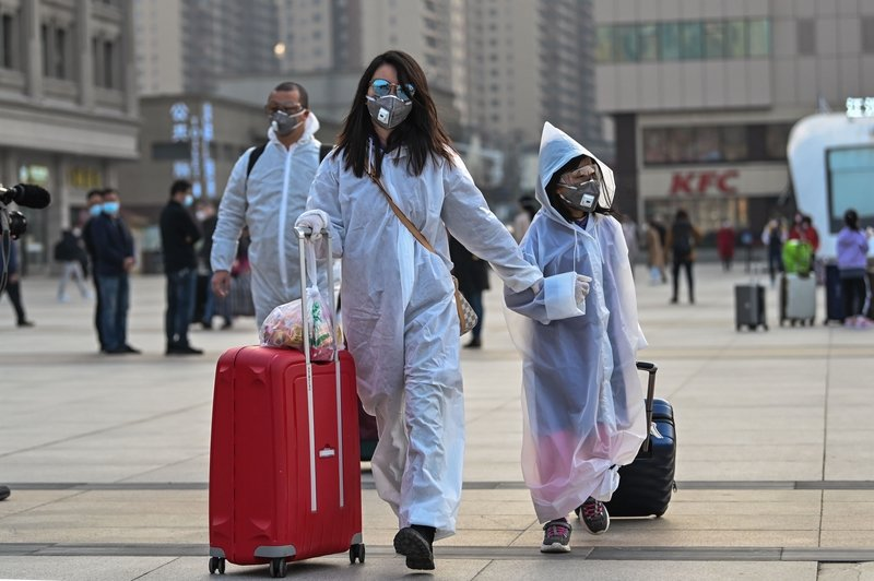 圖為2020年4月8日,湖北武漢火車站外準備搭車離開的民眾全副武裝。(HECTOR RETAMAL/AFP via Getty Images)