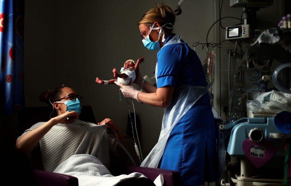 2020年5月15日,英格蘭伯恩利,國家衛生服務機構(NHS)工作人員正在對抗中共病毒(俗稱武漢病毒、新冠病毒),伯恩利綜合醫院的新生兒護士Kirsty Hartley從新生兒深切治療部將早產嬰兒西奧·安德森(Theo Anderson)交給母親科斯蒂·安德森(Kirsty Anderson)。(HANNAH MCKAY/POOL/AFP via Getty Images)