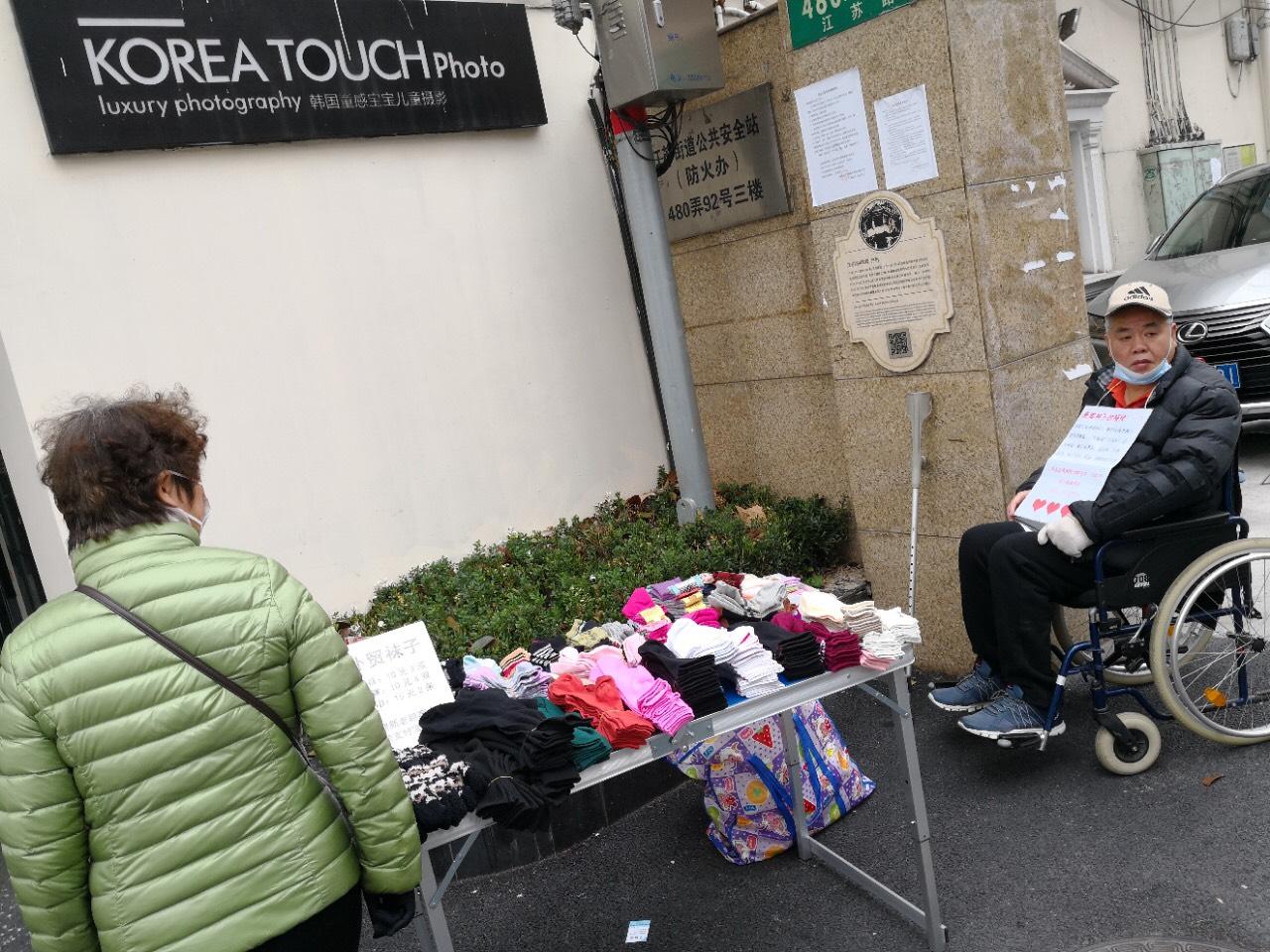 上海王扣瑪被兩次冤獄共四年,獄中致終身殘疾,如今又被停養老金和醫保卡,只能擺攤艱難度日。(受訪者提供)