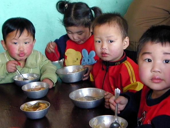 圖為一群北韓的小孩在吃捲心菜午餐。(Getty images)