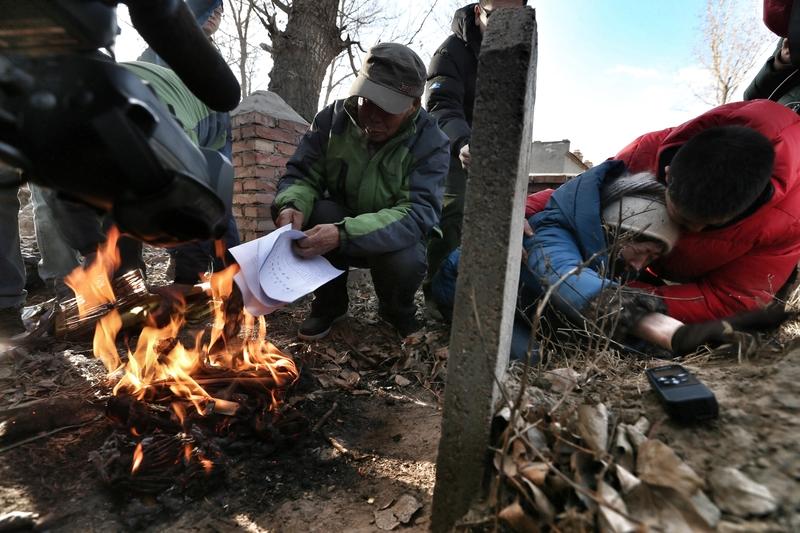 圖為2014年12月15日,呼和浩特,呼格吉勒圖案再審被判無罪,內蒙古自治區高級人民法院向申訴人、辯護人、檢察機關送達了再審判決書。家人在其墳前燒判決書複印件。(大紀元資料庫)