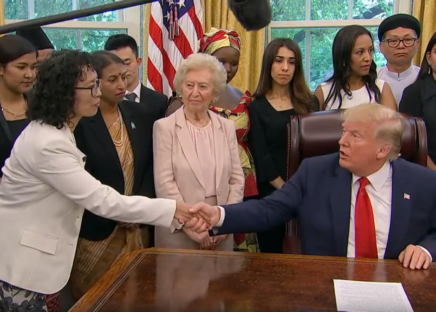 周三(7月17日)下午,美國總統特朗普在白宮與來自中國、土耳其、北韓、伊朗和緬甸在內的17個國家的宗教迫害倖存者會面,其中包括法輪功學員張玉華(左一)。(白宮影片截圖)