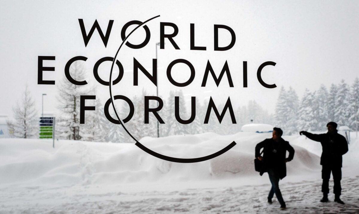 2018年1月22日,瑞士達沃斯,世界經濟論壇年會開幕前,一名保安在達沃斯會議中心外為一名男子指路。(Fabrice Coffrini/AFP via Getty Images)