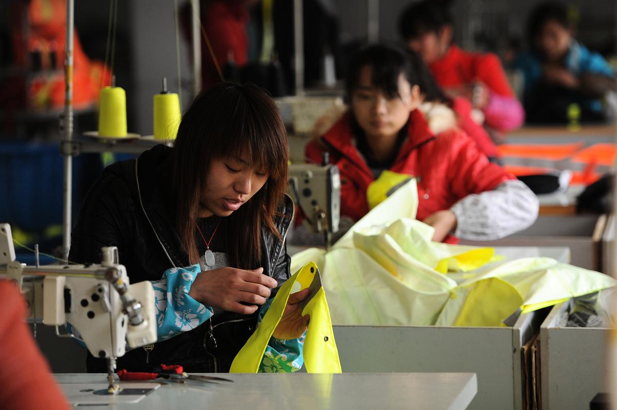 中國大宗商品的漲價潮已經向下游蔓延,企業陷入接單「兩難」境地。圖為2011年2月24日合肥市一家紡織廠的工人正在工作。(AFP/AFP via Getty Images)