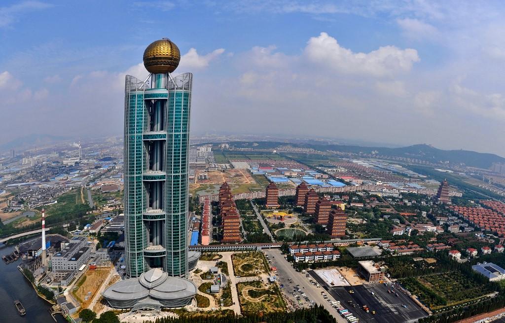 昔日「中國第一村」華西村和「中國第一民企」蘇寧,如今瀕臨債務危機,搖搖欲墜,預兆中國民營經濟前途黯淡,中共加快「國進民退」的收割。圖為華西村及其標誌性建築龍希國際大酒店。(STR/AFP)