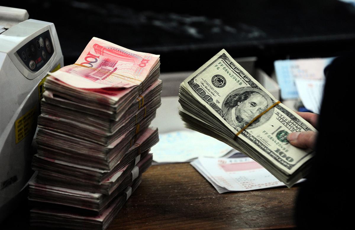 圖為2010年3月9日,安徽省合肥市一家銀行的員工在點收人民幣和美元。(STR/AFP/Getty Images)