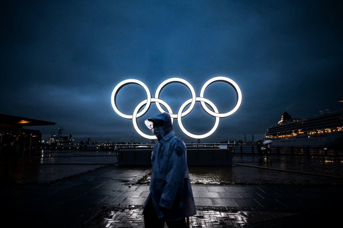 2021年7月2日,日本橫濱一名男子在黃昏時分經過奧運五環。(PHILIP FONG/AFP via Getty Images)