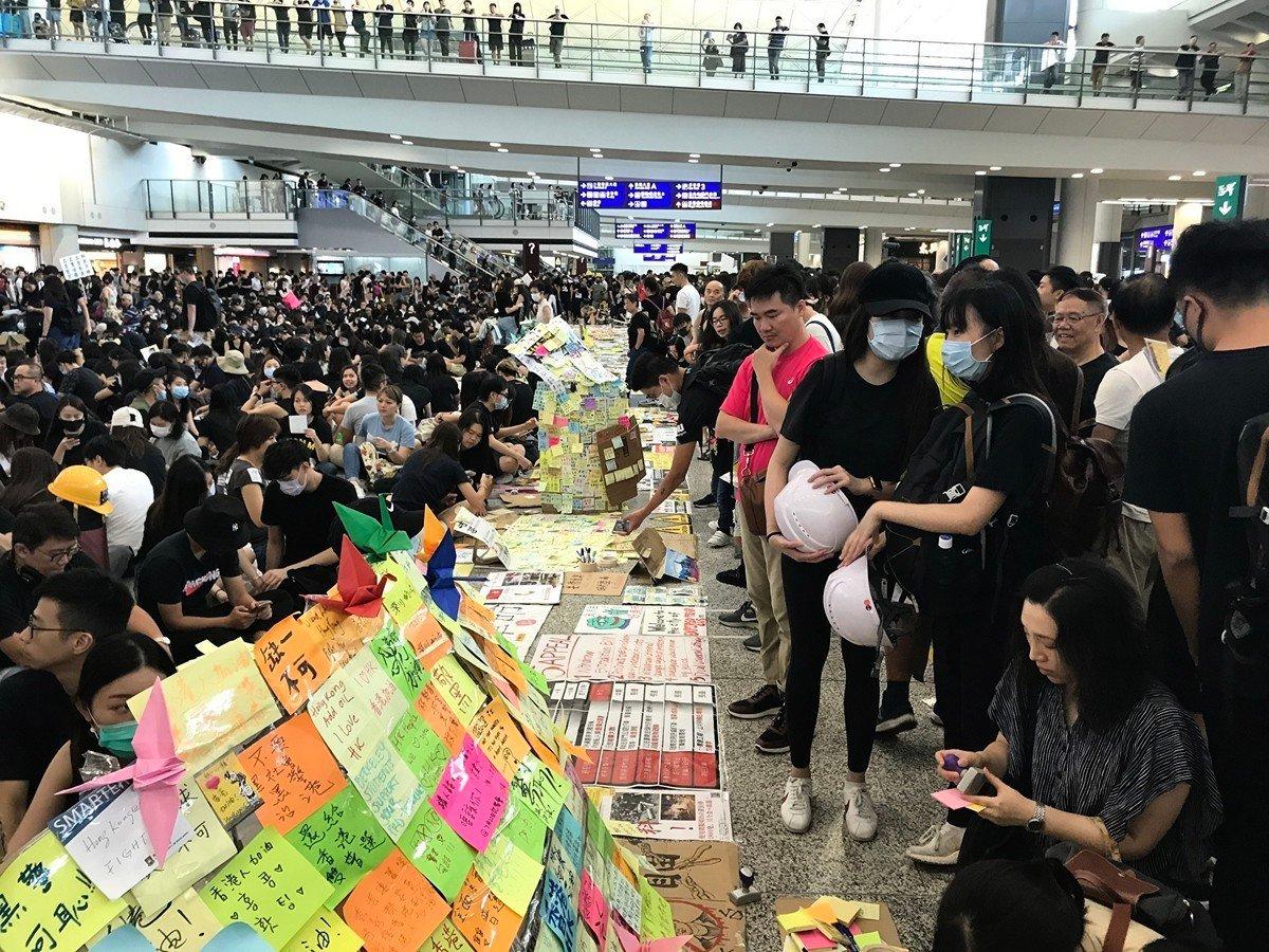 2019年8月10日,香港機場「萬人接機」活動進入第二天,集會人士將寫有不同語言的海報、傳單擺放在地上供人閱覽,同時也設立連儂牆。(林卓楷/大紀元)