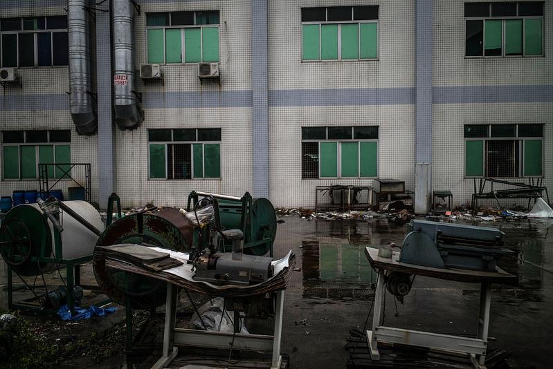 中美貿易戰不斷升級,也重創了在中國境內的外企,包括六成日本在華企業已經或正在撤出中國。圖為東莞一家倒閉的工廠的設備被遺棄在外面。(Lam Yik Fei/Getty Images)